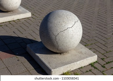 Stone balls on a city street. City design of the square. A ruler of large street decorative in large cracks of natural granite spheres. Cracks on the surface of a granite stone sphere