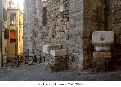 Stone basins resting on the ancient wall and bicycle in the historic center of Portovenere