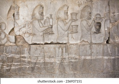 Stone bas-relief with ancient people holding food and edged weapons in Persepolis, Fars Province, Iran