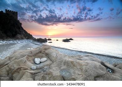 Stone beach with stone eggs  at sunset i Tusa Sicily