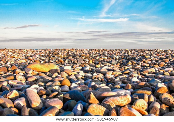 Stone beach. Large and small smooth stones. The sun at sunset