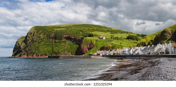Stone beach and row of white houses of Pennan coastal fishing village on North Sea in Aberdeenshire Scotland UK with Black Hill sea cliff