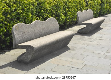 stone benches along a hedge