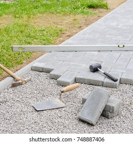 Stone blocks with tool for paving laying down background. Hausework architect concept
