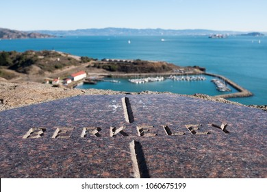 Stone board at Vista Point, by the Golden Gate bridge in San Francisco, overlooking Horseshoe bay, with letters reading BERKELEY, pointing towards the city of Berkeley, on a bright sunny day