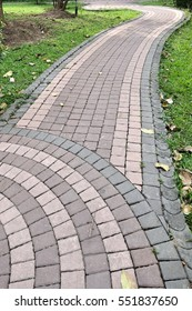 The Stone brick block walk path in the park with green grass