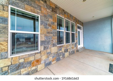 Stone brick wall windows and front door at the facade of a residential house