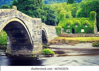 Stone bridge across the river Conwy, and old cottage covered with vine leaves, Llanrwst, Caernarfon, North Wales.