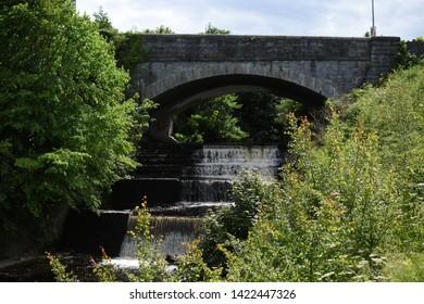 A stone bridge crossing over a waterfall in Dublin, Ireland.