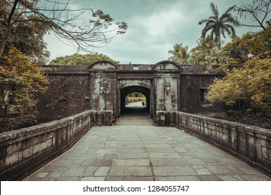 The stone bridge leading to the Fort Santiago entrance. Intramuros historic walled area. Manila, Philippine. Ancient Spanish landmark surrounded by the wild nature. The popular tourist attraction.