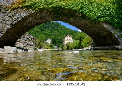Stone bridge, mountain river and alpine town in Slovenia. Summer scene in Julian Alps