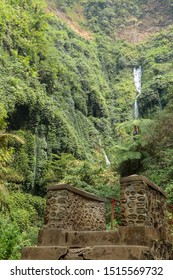 Stone bridge over the river at the waterfall. Steep walls of the valley covered with dense tropical vegetation. 200 meters tall Air Terjun Madakaripura waterfall on Java island in Indonesia.