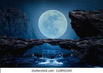 A stone bridge with a waterfall on the beautiful full moon night.
