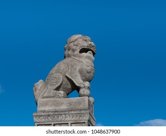 Stone Buddhist lion guard Shi-dza in the paw holds a ball, symbolizing Buddhist knowledge, bringing light to darkness and able to fulfill desires