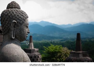 Stone budhha sideview in front of two stupas at Borobudur near Yogyakarta in Indonesia.