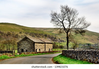A stone built barn and solitary tree at the side of a country lane in the Yorkshire Dales, England, set again a backdrop of fells