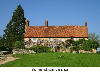 Stone built wisteria clad traditional cottage in rural Oxfordshire England