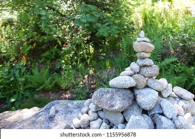Stone cairn against a green background with empty space on the left, showing the right direction on the GR10 trail in the Pyrenees mountain range, France