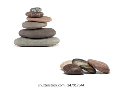 Stone cairn made from a variety of colorful Lake Superior rocks.  Four extra stones in foreground. Studio shot.  Isolated on white.