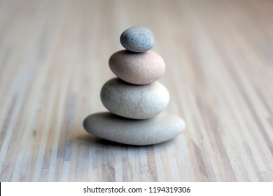 Stone cairn on striped grey white background, three stones tower, simple poise stones, simplicity harmony and balance, rock zen sculptures