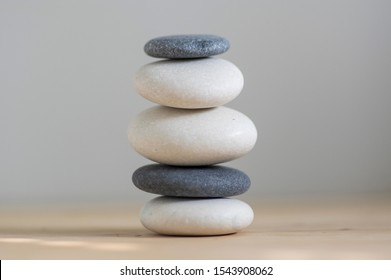 Stone cairn on wood background, stones tower, simple poise stones, simplicity harmony and balance, rock zen sculpture, black and white pebbles