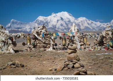 Stone cairn with Tibetan Buddhist prayer flags and yak horn marks a religious place of Tong La mountain pass (5,150 metres) on China-Nepal Friendship Highway, Shishapangma Mountain in background.