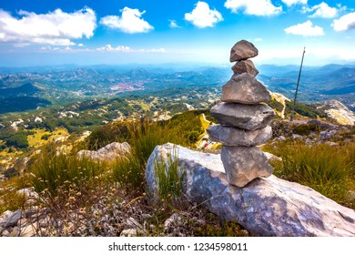 Stone cairns pyramid built on top of a mountain with a panoramic view of the Montenegrin valley of hills and forests under a blue sky with white clouds. Vidikovac, Lovcen National Park, Montenegro.