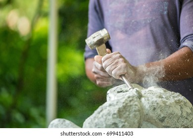 stone carver hitting the carving tool