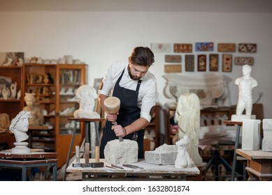 Stone carver works with wooden hammer and chisel at limestone.