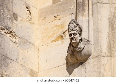 Stone carving of a bishop on the outside wall of Winchester Cathedral