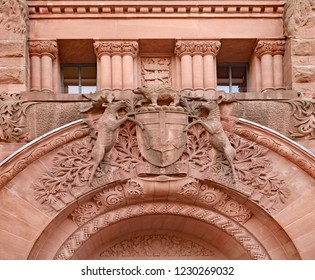 "Stone carving of the coat of arms of the Province of Ontario above the door of the legislature building, with the Latin motto ""She remains faithful as she began."""