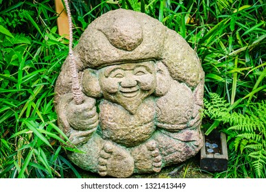 Stone carving of Ebisu one of seven deities of good fortune stands in a traditional Japanese garden