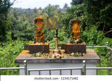 Stone carving of a naga (Snake god) and traditional south Indian brass oil lamp (Nilavilakku) near temple in kerala.