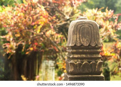 Stone carving pillar on background of colorful bushes. Oriental style.