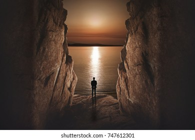stone cave's tiny exit gate over a sea sunset