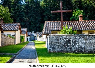 Stone cells and walls in monastery courtyard. Stone path to chapel. Camaldoli monastery, Tuscany, Italy.
