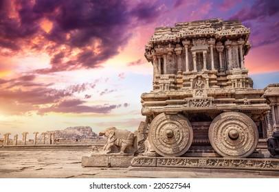 Stone chariot in courtyard of Vittala Temple at sunset purple sky in Hampi, Karnataka, India