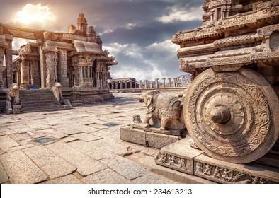 Stone chariot in courtyard of Vittala Temple at sunset overcast sky in Hampi, Karnataka, India
