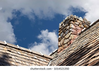 Stone Chimney:  Powerful view of a stone chimney on a thatched roof against a cloudy sky.