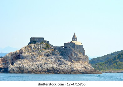 A stone church and fortress cover the top of a rocky island in the Mediterranean. Tree-covered hills are in the distance. The sky is blue.