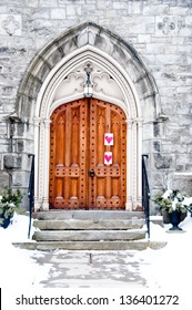 A stone church with an ornate wooden door has hearts hung to one side.