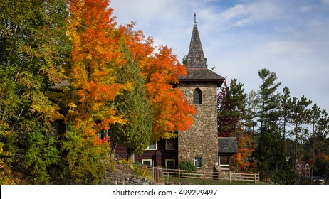 A stone church steeple surrounded by colorful autumn foliage on a sunny fall day in the village of Lake Placid, New York