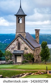 Stone church at top of the rock in Branson, Mo with mountains and lake behind it. Stone church on top of the golf course with clouds.