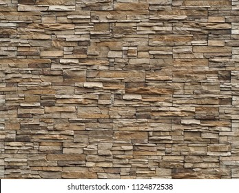Stone cladding wall made of  striped stacked slabs of natural brown rocks. Panels for exterior .
