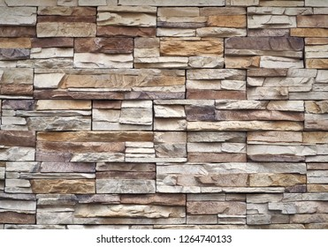 Stone cladding wall made of  striped stacked slabs of  multicolor natural rocks. Panels for exterior .