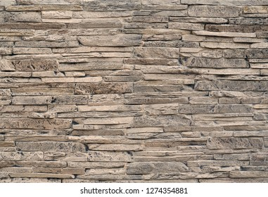 Stone cladding wall made of  striped stacked slabs of natural brown rocks stained with black .
