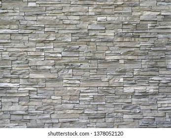 Stone cladding wall made of  striped stacked slabs of natural gray rocks. Panels for exterior .