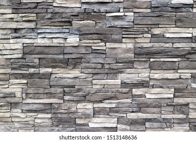 Stone cladding wall made of  striped stacked slabs of natural rocks. Colors are dark gray and white, background and texture