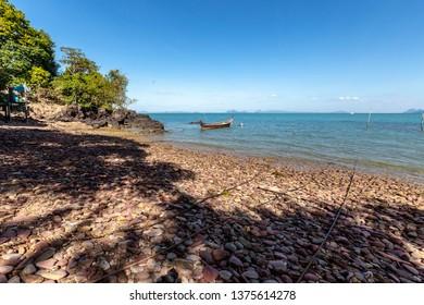 The stone and coarse sand and fishing boat beach at Koh Lanta, Krabi, Thailand.