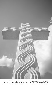 Stone cross decorated with traditional Croatian historic interlace or wattle pattern, artistic black and white edit with copy space for text.
